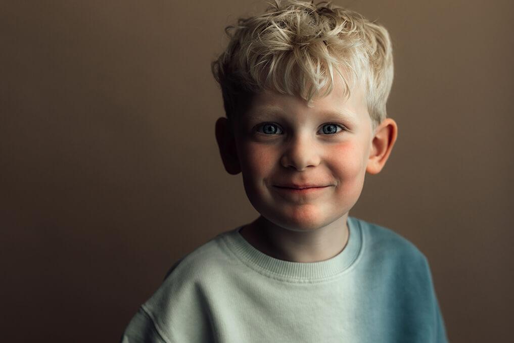lachende jongen portret op bruine achtergrond