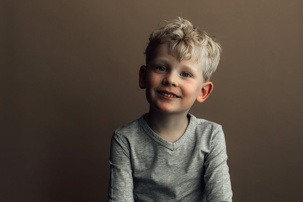 lachend kinderportret op bruine achtergrond