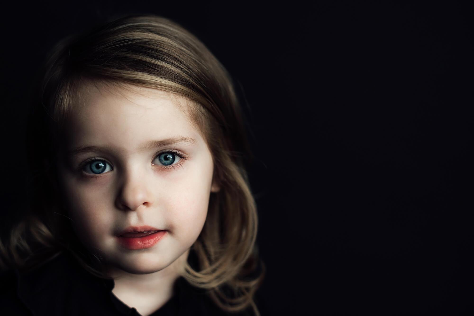 een portret van een kind op zwarte achtergrond. Samen met haar moeder.