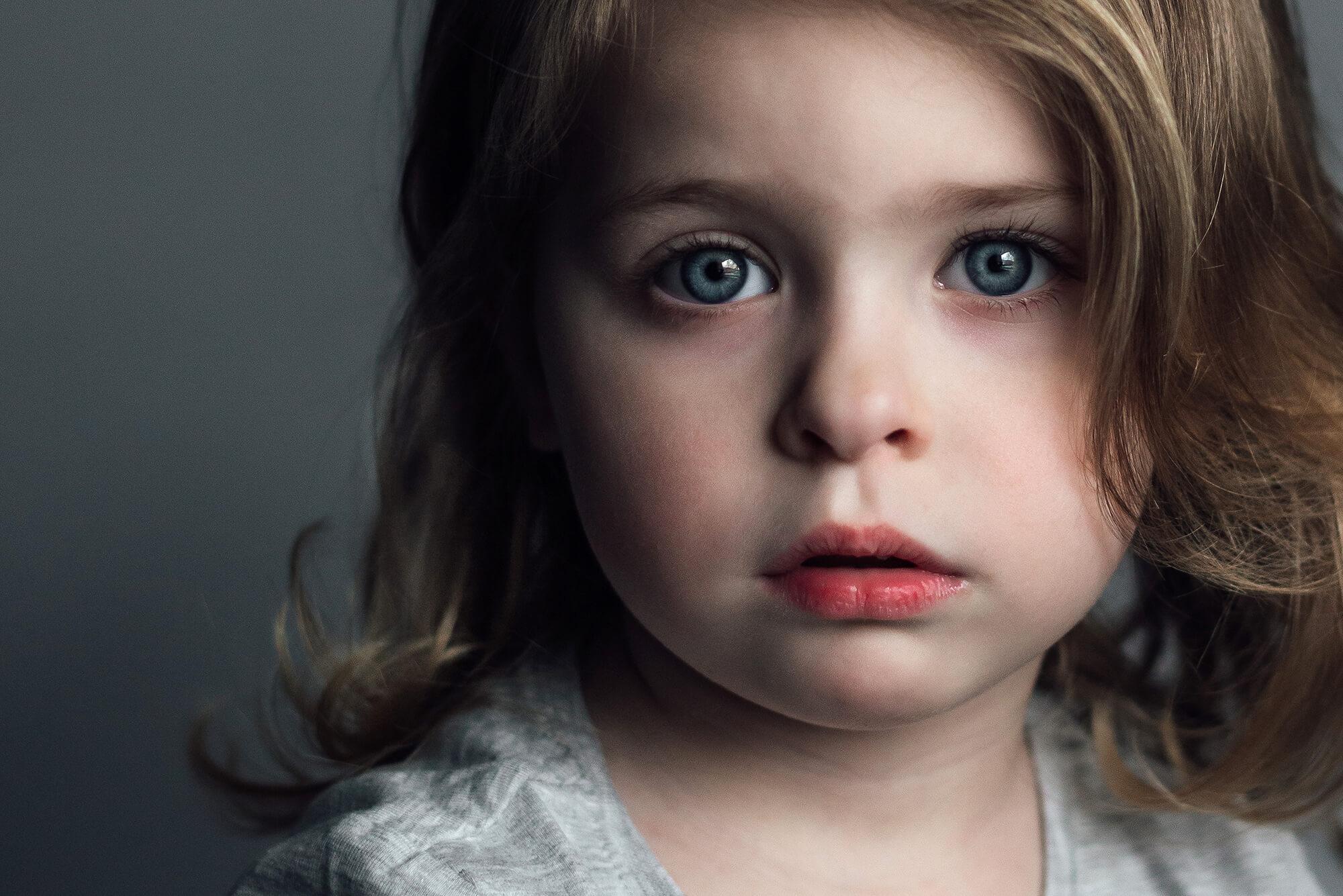 een portret van een kind op grijze achtergrond. Samen met haar moeder.
